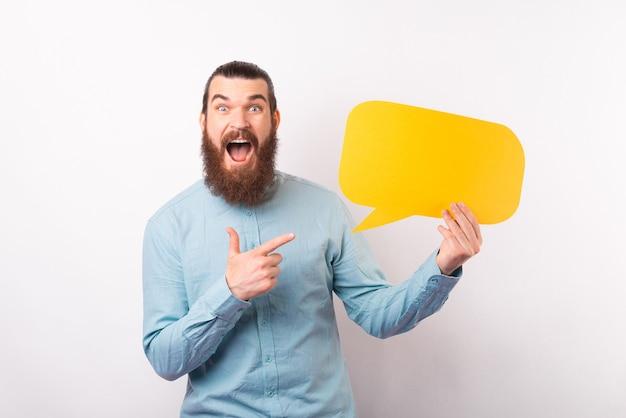 Verbaasde bebaarde man schreeuwen en wijzend op lege gele tekstballon