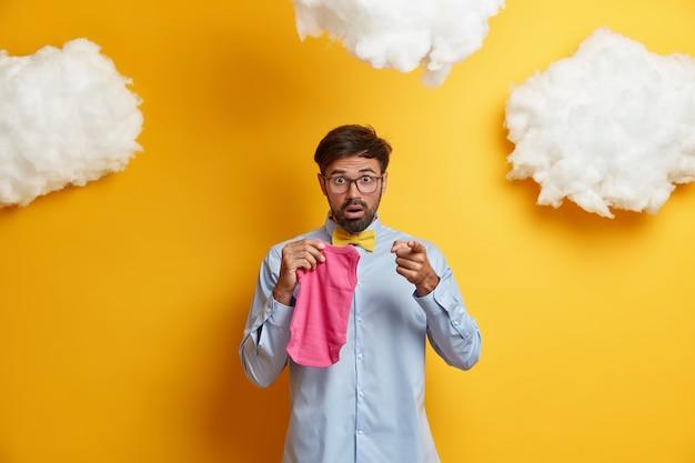Verbaasde bebaarde toekomstige vader wijst direct, komt schokkend nieuws te weten, klaar voor ouderschap en faterhood, poseert met roze bodysuit, doet boodschappen en koopt kleding voor pasgeborenen