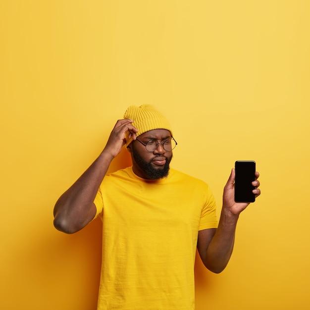 Verbaasde, bedachtzame man krabt zijn hoofd, denkt na over het maken van een nieuwe applicatie, laat je smartphonescherm zien, gekleed in gele kleding