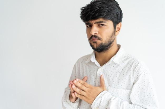 Verbaasde betrokken indische kerel die over probleem denkt.