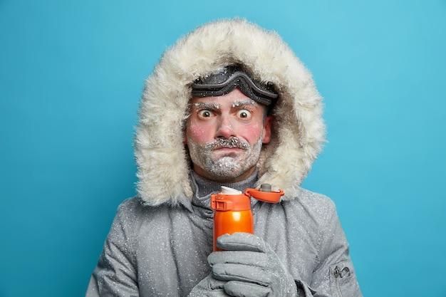 Verbaasde bevroren man in winterkleren probeert zichzelf op te warmen met warme drank heeft een rood gezicht en beer bedekt met sneeuwstorm brengt veel tijd buiten door tijdens het snowboarden. ijzige weersomstandigheden