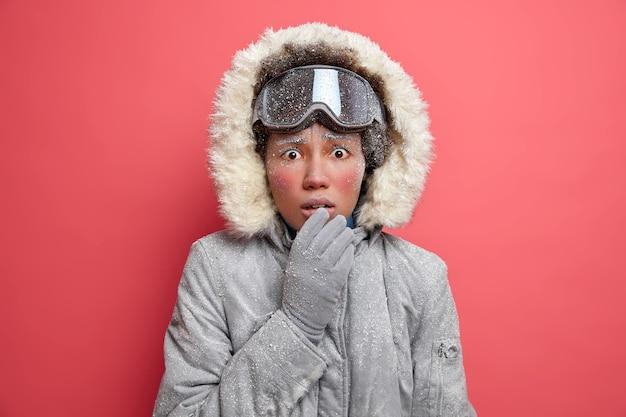 Verbaasde bevroren vrouw met rood ijskoud gezicht kijkt beschaamd trilt van kou draagt skibril grijze jas gaat wandelen in stormachtig sneeuwweer