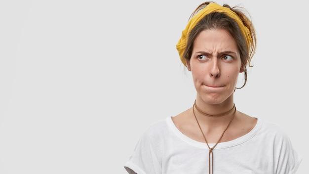 Verbaasde blanke vrouw houdt lippen ingedrukt, heeft gezichtsuitdrukking gefrustreerd, fronst gezicht van ongenoegen, diep in gedachten