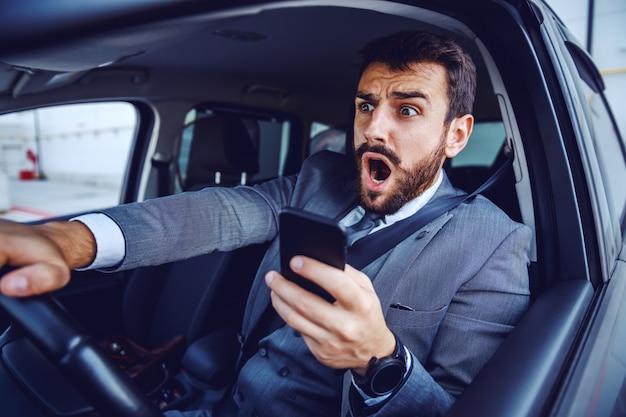 Verbaasde blanke zakenman in pak autorijden en tegelijkertijd slimme telefoon gebruiken.