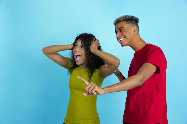 Verbaasde blik op de zijkant als sportfans. jonge emotionele afro-amerikaanse man en vrouw in kleurrijke kleding op blauwe achtergrond.