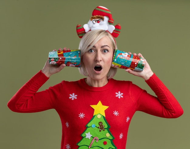 Verbaasde blonde vrouw van middelbare leeftijd die de hoofdband van de kerstman en kersttrui draagt en plastic kerstkopjes naast de oren houdt, luisterend naar gesprekken die geïsoleerd op een olijfgroene muur kijken