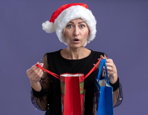 Verbaasde blonde vrouw van middelbare leeftijd met een kerstmuts die kerstcadeautassen vasthoudt die er een openen die geïsoleerd op een paarse muur kijkt