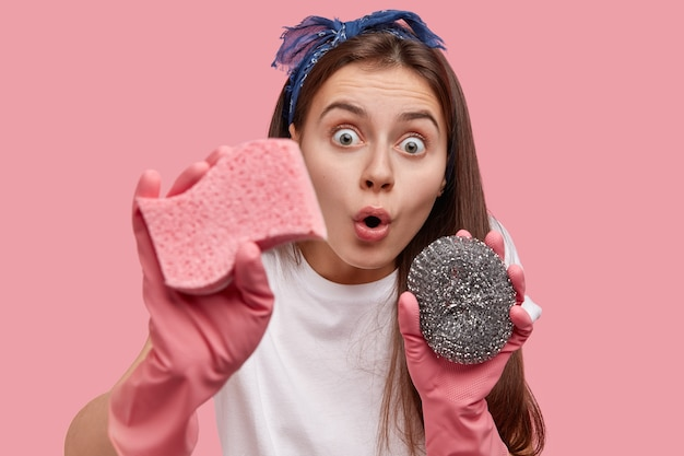 Verbaasde brunette dame met schoonmaakgereedschap, ogen uitgesprongen, geschokt om veel vuil te zien