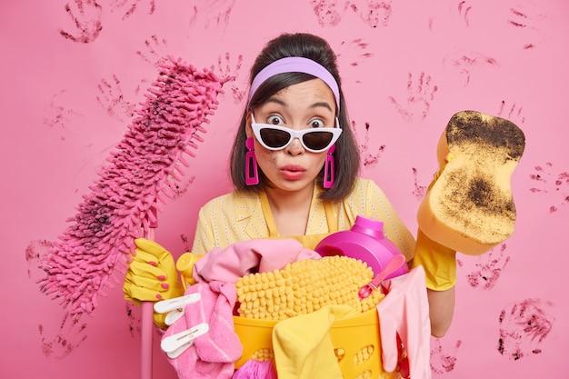 Verbaasde brunette huisvrouw kijkt geschokt naar camera veegt stof af en maakt vloer schoon met dweil bezig met huishoudelijke klusjes poses tegen roze muur met vuile handafdrukken