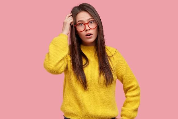 Verbaasde brunette vrouw krabt hoofd, ziet er verrassend uit, draagt een bril en gele kleren