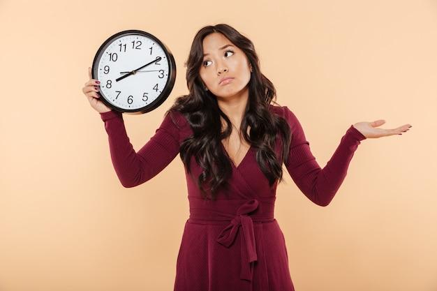 Verbaasde brunette vrouw met krullend lang haar met klok met tijd na 8 gebaren alsof ze te laat is of niet om perzikachtergrond geeft