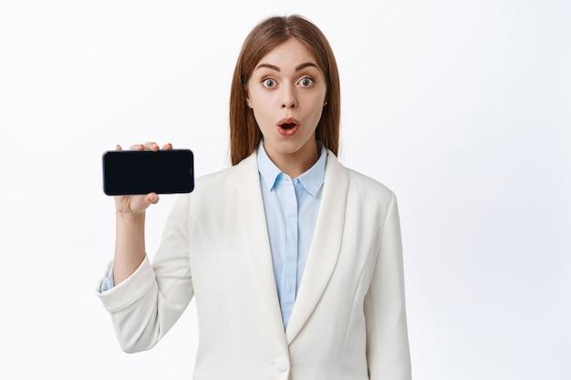 Verbaasde ceo-kantoorvrouw in pak toont mobiel scherm, houdt de telefoon horizontaal en demonstreert een leeg display, witte muur