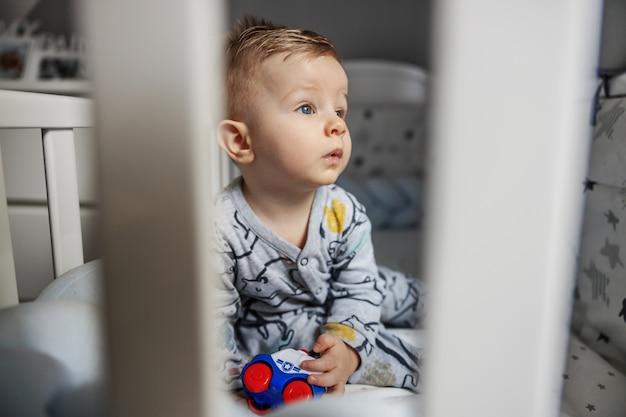 Verbaasde charmante blonde babyjongen die 's ochtends in zijn wieg zit, zijn speeltje vasthoudt en wegkijkt.