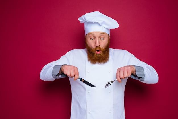 Verbaasde chef-kok met baard en rode schort is klaar om te koken