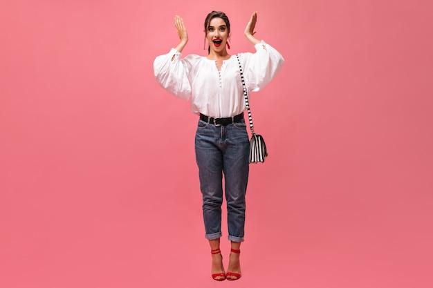 Verbaasde dame in stijlvolle outfit kijkt naar de camera op roze achtergrond. verraste vrouw in wit wijd overhemd met gestreepte handtas en rode lippen vormt.