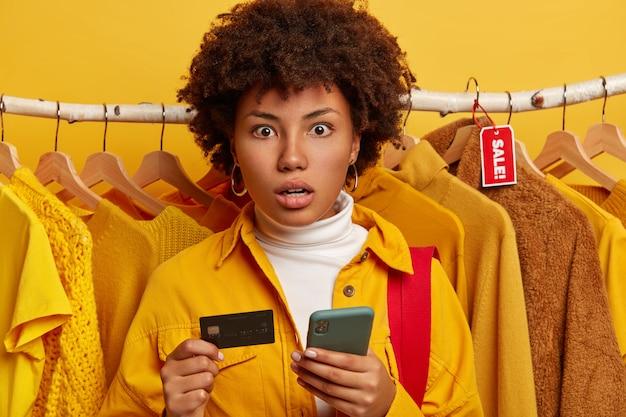 Verbaasde dame met afro-kapsel, gekleed in een geel overhemd, poseert boven kledingrekken, houdt moderne mobiele telefoon en creditcard vast