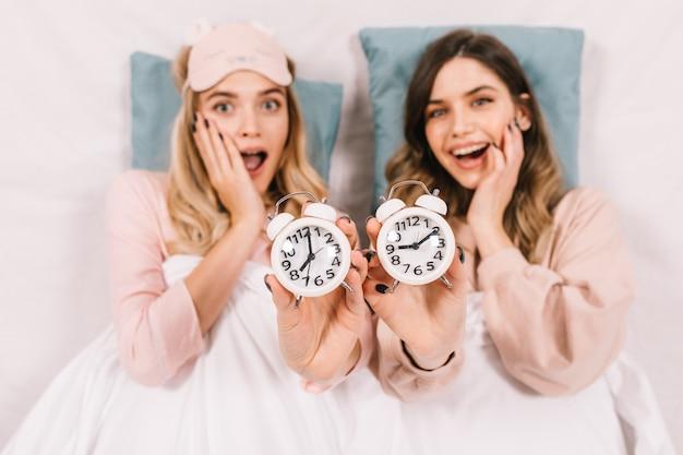 Verbaasde dames poseren in bed met klokken