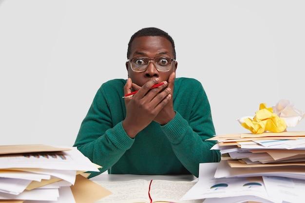 Verbaasde donkere tekstschrijver houdt handen op mond, draagt pen, schrijft iets in notitieblok, preapres rapport na analyse van documenten