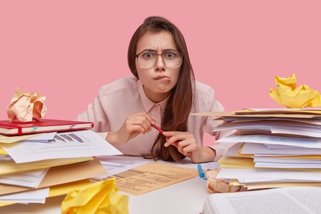 Verbaasde donkerharige dame tuit haar lippen, omringd door stapels documenten, volgt opfriscursus, draagt een optische bril