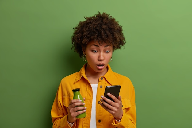 Verbaasde duizendjarige vrouw met krullend haar staart naar het scherm van de smartphone, leest schokkend nieuws, drinkt spinazie-smoothie, gebruikt draadloos internet, gekleed in gele kleren, poseert tegen de groene muur