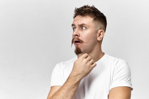 Verbaasde emotionele hipster-man met stuursnor en stoppelbaard die de mond opent in shock en verbazing, verrast met slecht schokkend nieuws. gefrustreerde verbaasde bebaarde man die zich voordeed in de studio