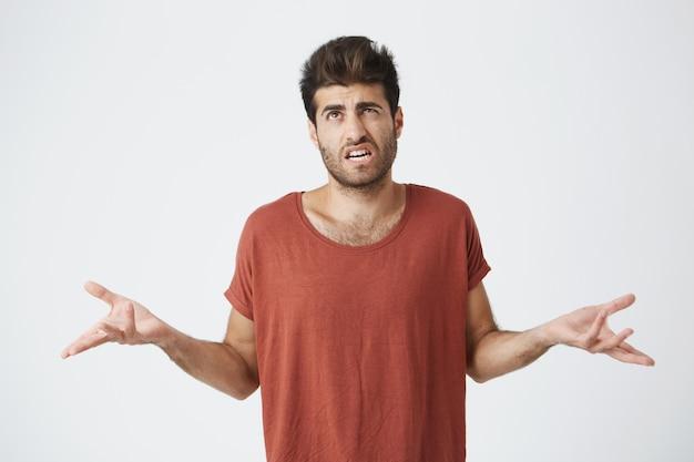 Verbaasde en clueless bebaarde man met stijlvol kapsel gekleed in vrijetijdskleding schouderophalend en starend met verwarde blik nadat hij een fout had gemaakt maar zich daar niet schuldig over voelde