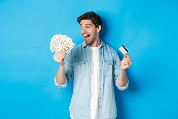 Verbaasde en gelukkige man met creditcard, tevreden kijkend naar geld, staande over blauwe achtergrond