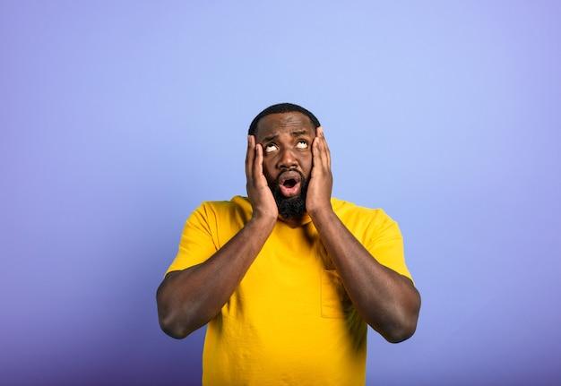Verbaasde en geschokte uitdrukking van een man op een paarse achtergrond