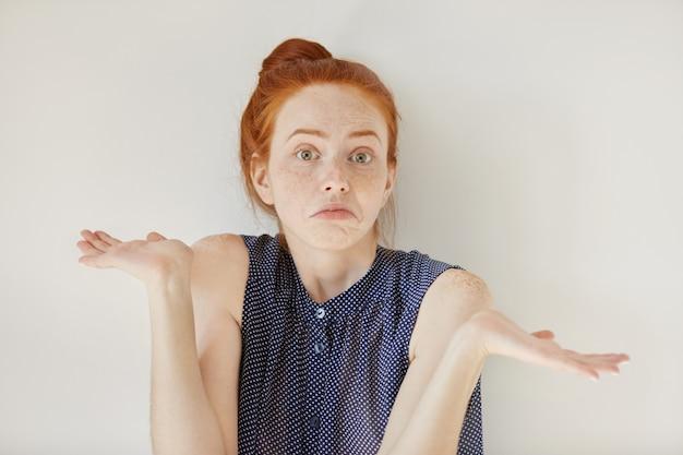 Verbaasde en onwetende jonge roodharige vrouw met uitgestrekte armen, schouderophalend zeggend: who cares, so what, ik weet het niet. negatieve menselijke emoties, gezichtsuitdrukkingen, levensperceptie en houding