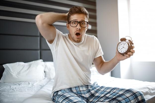 Verbaasde en scarec jonge man op bed in de ochtend. hij kijkt emotioneel op camera. man houdt klok in de hand.
