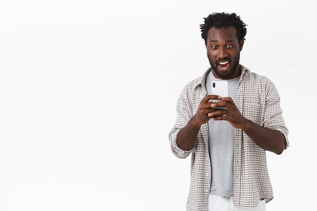 Verbaasde en verbaasde afro-amerikaanse bebaarde man die een geweldige video opneemt