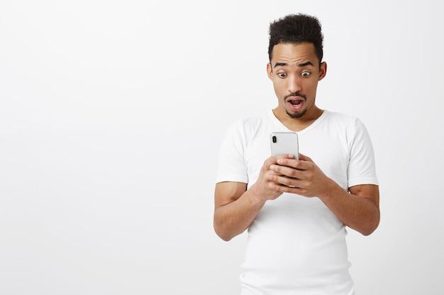 Verbaasde en verbaasde afro-amerikaanse kerel die naar adem snakt, kijkend naar het smartphonescherm, verbaasd over groot nieuws, geweldige applicatie