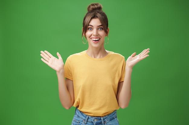 Verbaasde en verbaasde vrouw die reageert op een verbazingwekkend geschenk dat zijn handen opheft in de buurt van de schouders, vrolijk glimlachend naar de camera, opgetogen en tevreden met geweldige verrassing gemaakt door vrienden over groene muur.