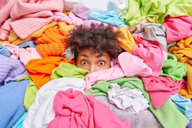Verbaasde etnische jonge vrouw met krullend haar die vastzit in een stapel wasgoed, doet huishoudelijk werk om items te vouwen. menselijk hoofd in enorme hoop ongevouwen kleding. opruimen van donatie en huishoudconcept