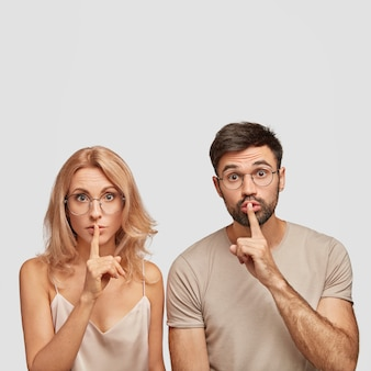 Verbaasde europese vrouw en man maakt zwijggebaar, vertelt vertrouwelijke informatie, vraagt stil te zijn
