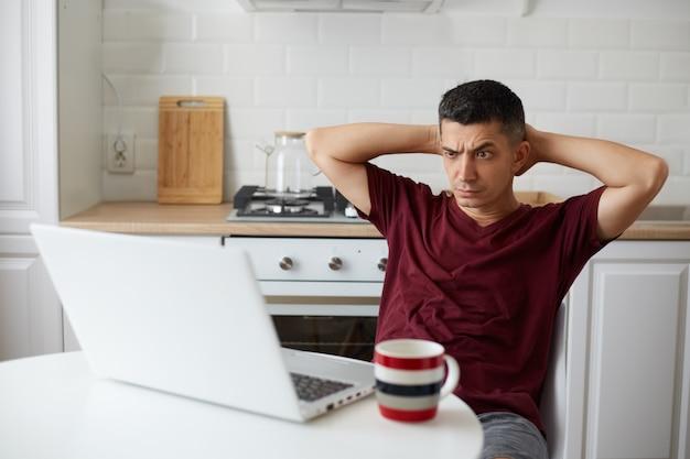 Verbaasde freelancer-man met casual kleding die voor een draagbare computer in de keuken zit, armen achter het hoofd houdt, naar het laptopscherm kijkt met een verwarde uitdrukking, een fronsend gezicht.