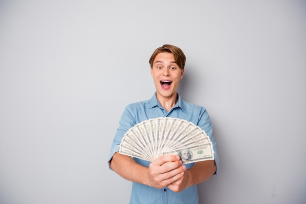 Verbaasde gekke kerel wint casino jackpot kijk op geld fan schreeuw