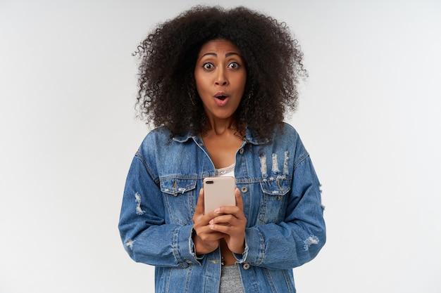 Verbaasde gekrulde donkere vrouw met casual kapsel en ronde ogen verrast, smartphone in opgeheven handen houdend, staande over witte muur