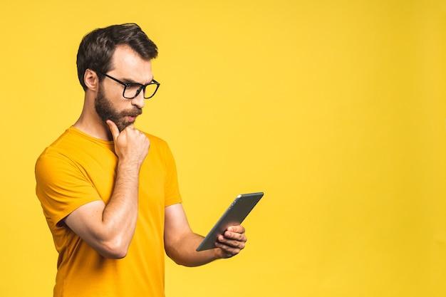 Verbaasde gelukkige bebaarde man die digitale tablet gebruikt en geschokt kijkt over nieuws op sociale media, verbaasde man shopper consument verrast opgewonden door online overwinning geïsoleerd op gele achtergrond.