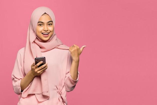 Verbaasde gelukkige jonge aziatische vrouw die een smartphone met behulp van en met vinger richt om ruimte te kopiëren