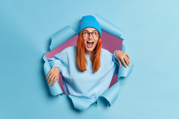 Verbaasde gelukkige vrouw kijkt met grote belangstelling opzij houdt mond open, draagt blauwe hoed en sweatshirt breekt door papieren gat