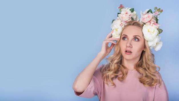 Verbaasde gepassioneerde dame met bloemen op kop
