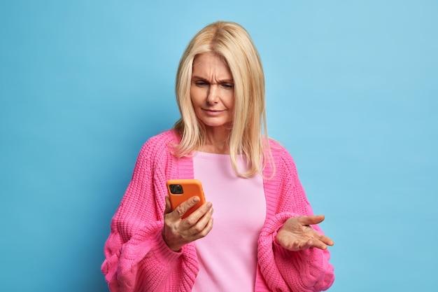 Verbaasde gepensioneerde vrouw gebruikt mobiele telefoon kijkt verward grijnzend gezicht omdat ze geen nieuwe applicatie kan downloaden gekleed in een casual trui.