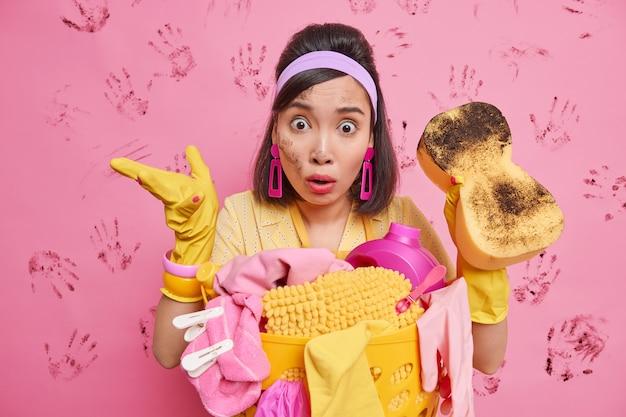Verbaasde geschokte brunette jonge aziatische vrouw draagt rubberen beschermende handschoenen met hoofdband verbijsterd om zo'n puinhoop en chaos in de kamer te zien, veel vuil houdt een spons vast om vuil te verminderen staat in de buurt van de wasmand