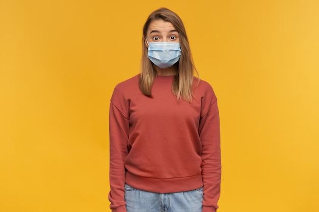Verbaasde geschokte jonge vrouw met virusbeschermend masker op gezicht tegen coronavirus staande over gele muur