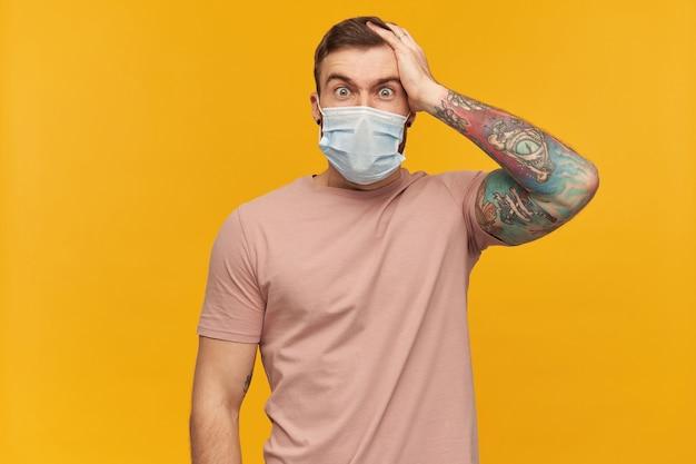 Verbaasde getatoeëerde jongeman in roze t-shirt en virusbeschermend masker op gezicht tegen coronavirus met baard houdt hand op het hoofd en kijkt geschud over gele muur