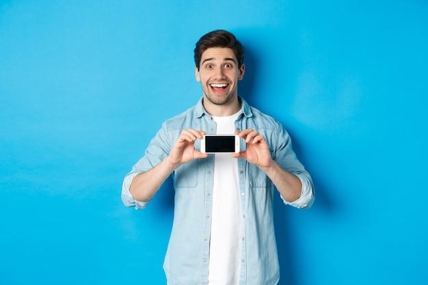 Verbaasde glimlachende man met smartphonescherm, internetpromo-aanbieding, staande tegen een blauwe achtergrond.