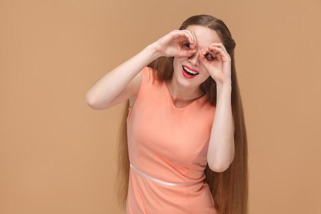 Verbaasde grappige vrouw die met verrekijkershanden camera bekijkt. emotionele schattige, mooie vrouw met make-up en lang haar in roze jurk. binnen, studio-opname, geïsoleerd op lichtbruine of beige achtergrond.