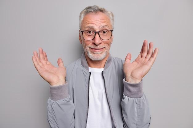 Verbaasde grijsharige senior man houdt handpalmen omhoog, voelt zich gelukkig en reageert zonder idee