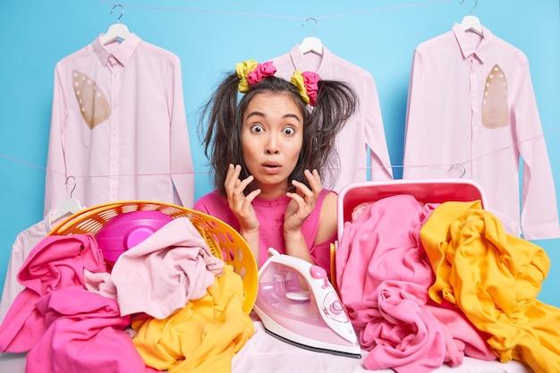 Verbaasde huisvrouw reageert op angstaanjagend nieuws steekt handpalmen op heeft veel wasgoed om te strijken staart verwarde ogen naar